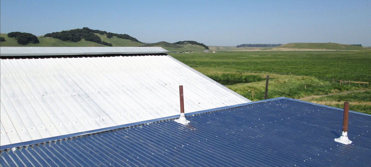 Roof top view of corrugated metal roof with backdrop of green rolling hills of Sonoma County